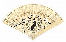 CHILD'S CELLULOID BRISÉ FAN Black-painted central vignette depicts a seated lady doing needlework in the style of a silhouette, flan..