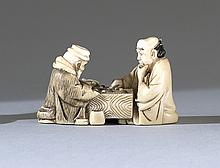 IVORY NETSUKE Depicting two sages playing Go. Signed on inlaid plaque. Length 2