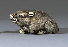 IVORY NETSUKE In the form of a recumbent boar with inlaid eyes. After Kaigyokusai. Length 2.25