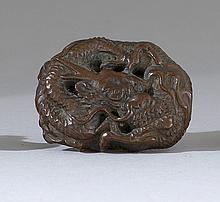 WOOD, LACQUER, AND IVORY MANJU In the form of a coiled dragon. Length 1.75