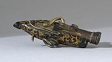 LACQUER, IRON, AND WOOD NETSUKE In the form of a pistol with movable hammer and scrolled foliate design. Inlaid iron barrel. Length...