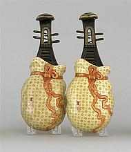 PAIR OF PORCELAIN WALL POCKETS In the form of musical instruments contained in brocade sacks. Lengths 10.5