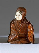 WOOD NETSUKE/OKIMONO Depicting a seated actor wearing an ivory okame mask. Height 1.75