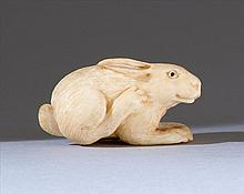 STAGHORN NETSUKE In the form of a resting rabbit with inlaid eyes. Length 1.7