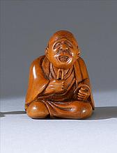 WOOD NETSUKE In the form of a seated man pulling whiskers from his chin. Height 1.4