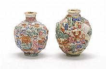 TWO MOLDED PORCELAIN SNUFF BOTTLES Both in ovoid form with four-character Qianlong marks. One with guardian lion design, height 2.4