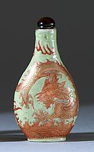 PORCELAIN SNUFF BOTTLE In teardrop form with coral-red and gilt dragon design on a green ground. Height 2.8