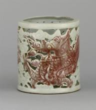 KOREAN UNDERGLAZE RED PORCELAIN BRUSH POT In cylinder form with pierced dragon and cloud design. Height 4.75