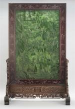 GREEN JADE TABLE SCREEN Mounted in hongmu stand. Jade carved with travelers and horses approaching a mountain fortress. Reverse with...