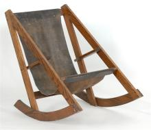 UNUSUAL ROCKING CHAIR Triangular oak frame with slung leather seat.