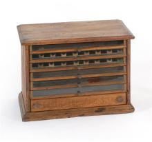 SPOOL CABINET In oak with molded top and six drawers with brass pulls.