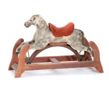 CHILD'S ROCKING HORSE Wooden horse painted black and white. Red velvet saddle. Wooden cradle painted red with yellow stencil decorat..