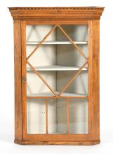 HANGING CORNER CUPBOARD In pine with molded pediment and through-mullioned glazed door enclosing three shelves. Height 42