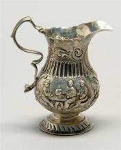 GEORGE II STERLING SILVER CREAMER In pear form with repouss? decoration of figures seated around a tavern table. Reverse double-scro...