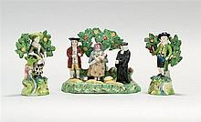 THREE-PIECE STAFFORDSHIRE FIGURAL GROUP Central group consists of three figures, including a woman holding a baby and a pig standing...