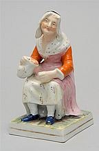 19TH CENTURY STAFFORDSHIRE FIGURE of Wife Nell. Modeled as a seated woman pouring from a pitcher. With polychrome and gilt decoratio...