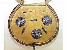 A cased set of three enamelled white metal buttons, with split rings, unmarked, each 11mm diameter.