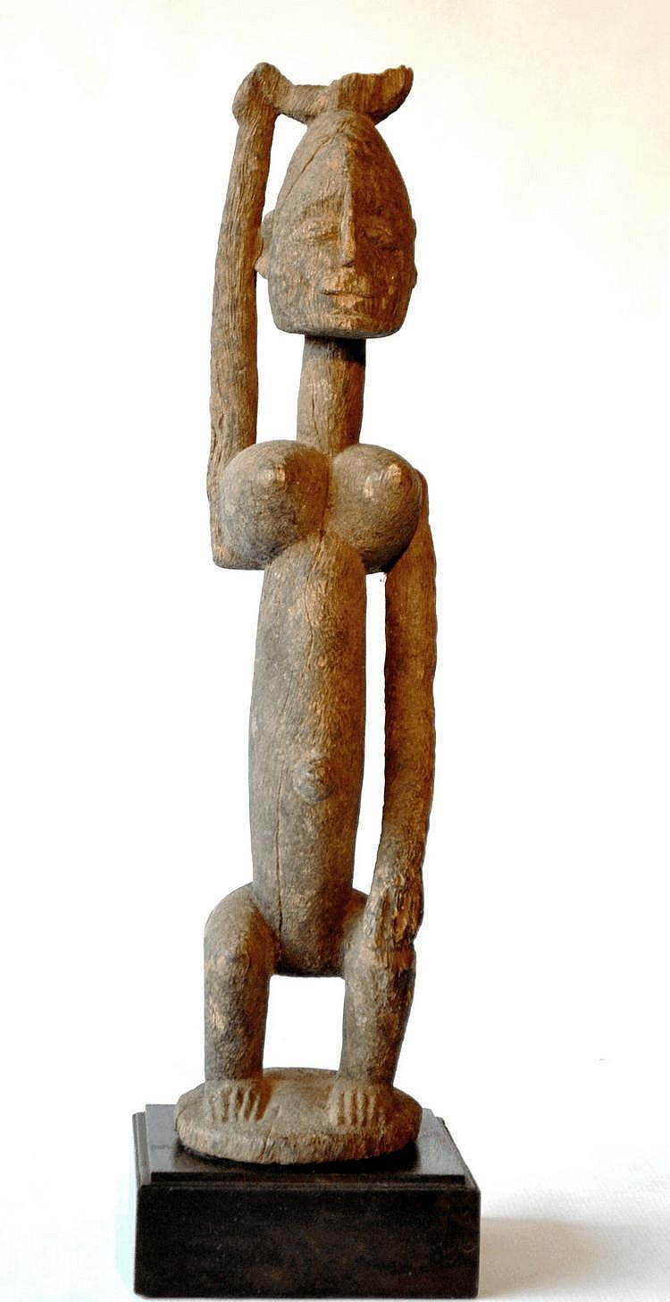 Mali, DOGON. Très ancienne statue féminine surmontée d'une petite coupe (petit manque) qu'elle porte sur le tête et qu'elle tient de la main droite. Les jambes sont fléchies et la main gauche repose sur le genou. Les seins sont généreux et l'ombilic