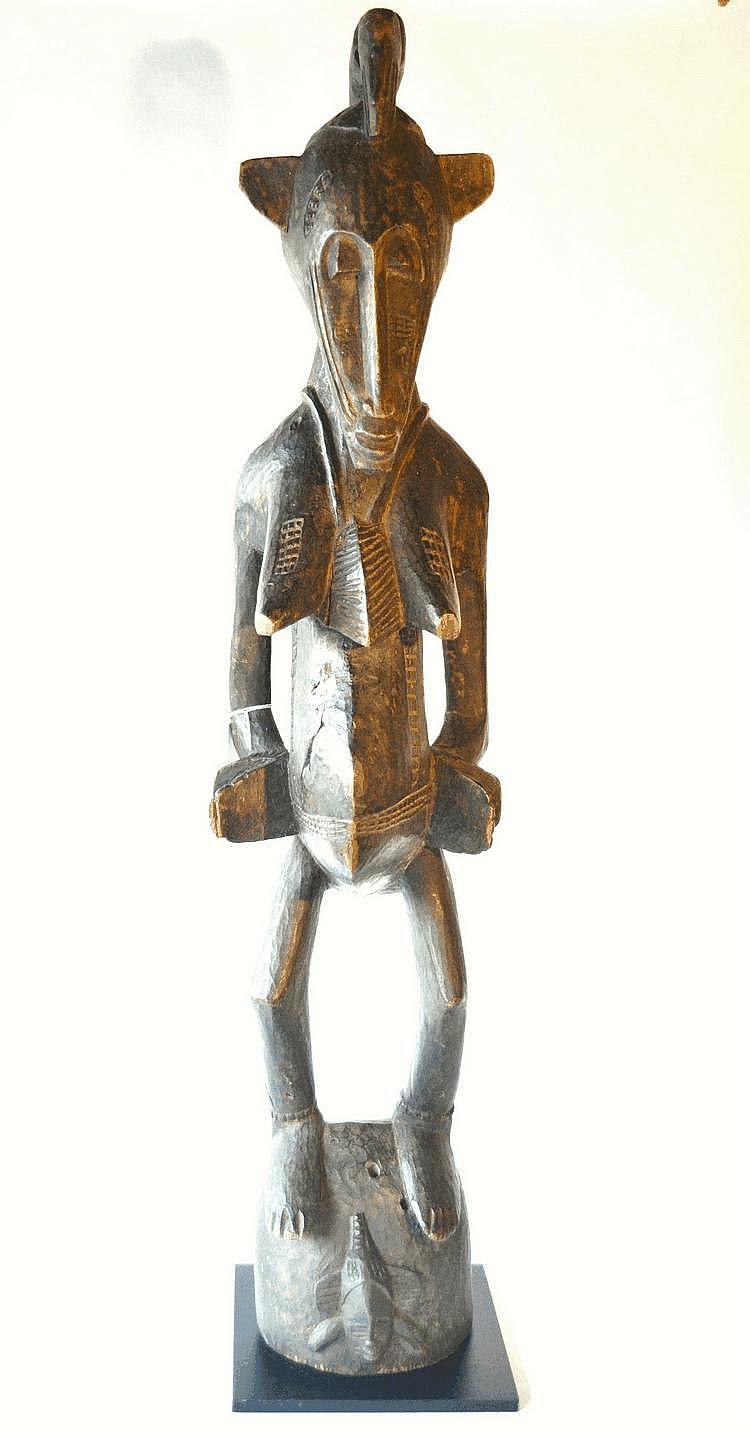 Côte d'Ivoire, SENOUFO. Rare et très belle statue féminine se tenant fièrement debout sur son socle. Les mains sont collées au corps et ouvertes. Le corps, le visage, le dos et les seins sont scarifiés. La tête est surmontée d'un animal dont la