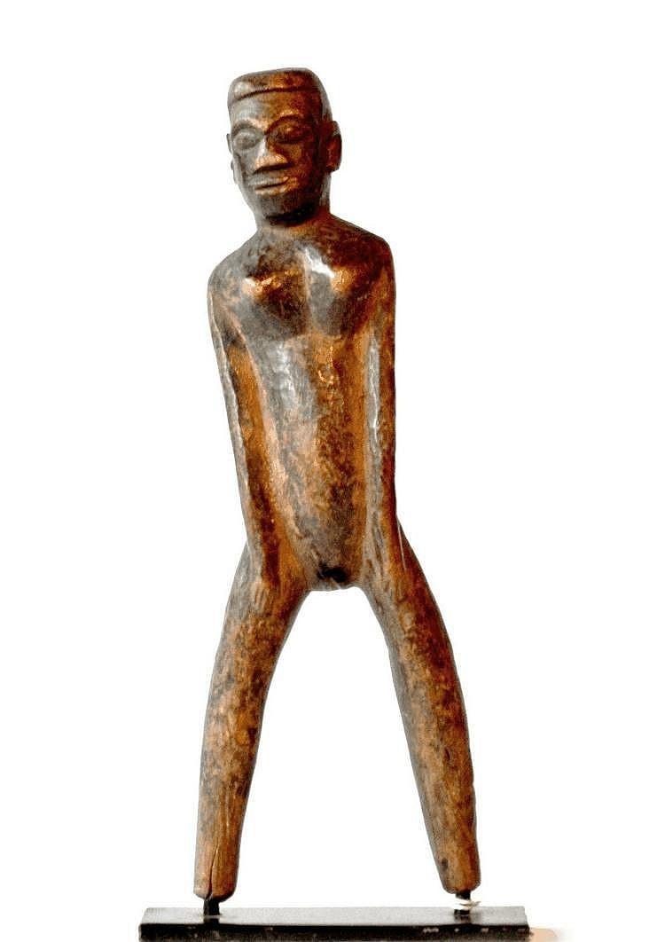Burkina-Faso,  LOBI. Lance-pierres représentant un personnage féminin se tenant debout. Les deux  mains, très féminines, sont posées sur les cuisses alors que le visage est, apparemment, celui d'un homme. Bois 21 cm
