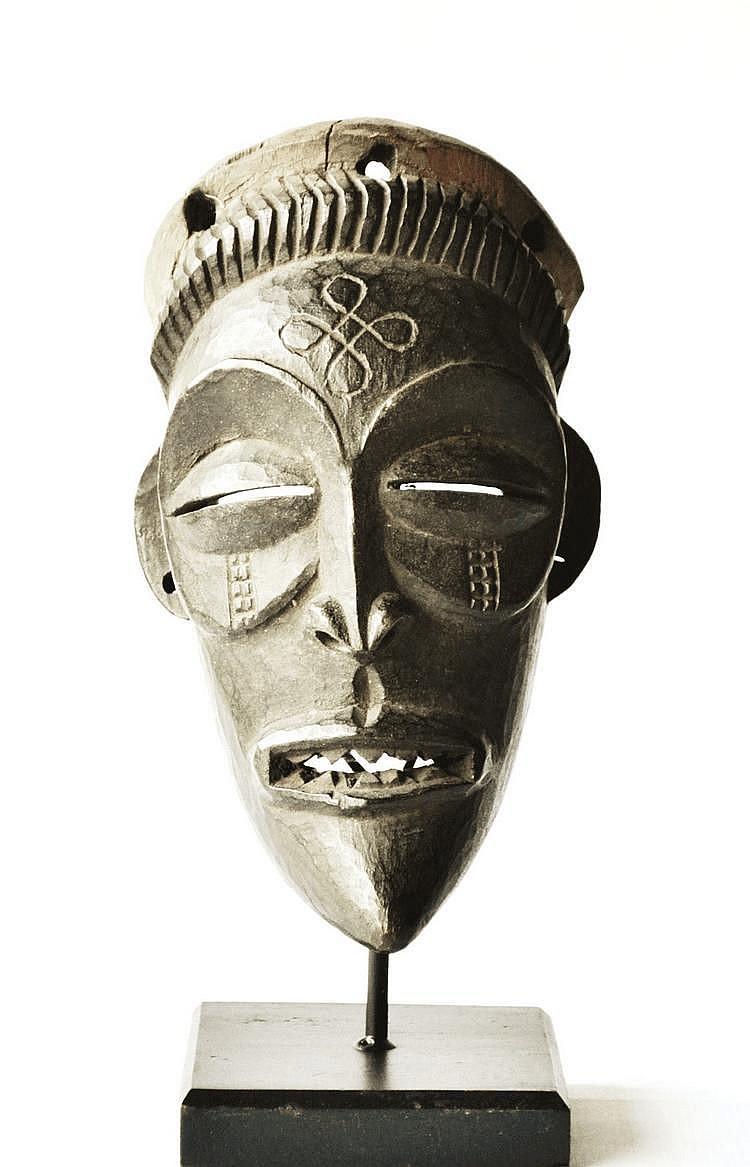 RDC,  TCHOKWE. Masque sculpté de façon très traditionnelle présentant une bouche largement ouverte et un menton en galoche. Belle patine d'usage. La coiffe est absente. Bois  21,5 cm