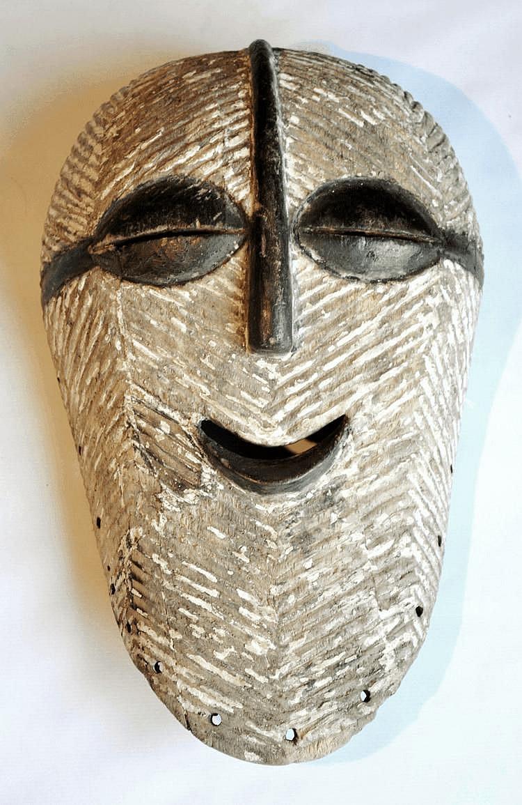 RDC, LUBA-SONGYE. Masque de danse des Luba-Songye qui a le mérite de sourire, ce qui est assez rare dans la statuaire Songye. Ce masque, très sympathique d'aspect, de forme ovale, est strié de lignes en chevron. L'arrête nasale, les grands yeux en