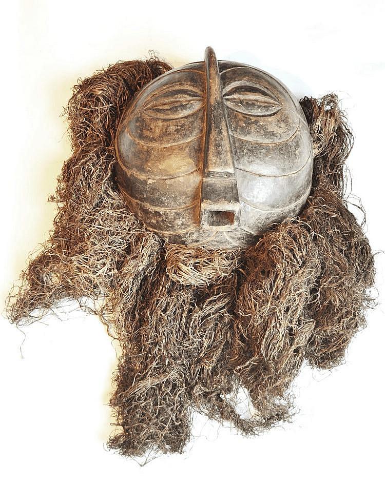 RDC, LUBA. Masque de danse rond Kifwele à stries, typique des Luba-Songye, offrant une belle patine foncée. Le nez ainsi que la bouche donnent beaucoup de force à l'expression de cette pièce fort intéressante. Une grande barbe de fibres accompagne le