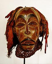 Masque de danse Mwana pow à visage féminin avec sa coiffe d'origine - Peuple TSHOKWE - RDC ou Angola (?) - Bois à très belle patine ancienne d'usage, tissus et tissus noués, fibres tricotées et fibres diverses - Dimension: H. 20 cm Provenance: Coll.