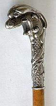 CANNE à pommeau en bronze argenté représentant une tête. Fût en cerisier