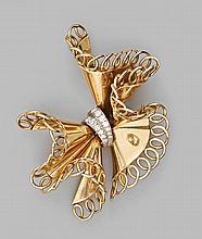 BROCHE noeud en or jaune à feston ajouré, le centre orné de diamants sertis sur