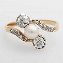Ring wohl um 1900, mit zwei Altschliff-Diam. zus. ca. 0,6ct, Weiß/ VS-SI/ PI, kleine Diam. zus. ca. 0,1ct, cremefarb. Zuchtperle (5,7mm)
