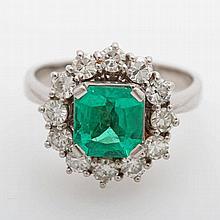 Damenring besetzt mit einem fac. Smaragd (ca. 8 x 7,7mm) entouriert von 12 Diam.-Brillanten zus. ca. 1,0ct WEIß/ VS-SI.