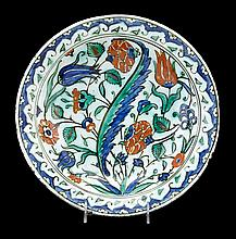 Iznik pottery plate, ottoman, turkey, circa 1590, The circular dished form decorated with carnations, tulips and saz in green, cobalt b