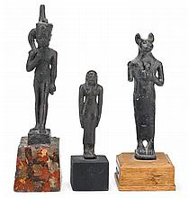Three Egyptian bronze figures, late period to ptolemaic period, 650-30 b.c., Depicting Bastet, Harpokrates, and an unidentified female,