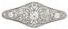 An Edwardian diamond and platinum brooch, , designed as a pierced navette form, set with an old European-cut diamond approximately: 0.8