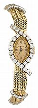 A diamond and eighteen karat gold wristwatch, Tiffany & Co., France, navette gold tone face with Roman numeral dial, signed Tiffany & C