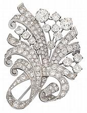 A Retro diamond and platinum spray brooch, circa 1950, surmounted by two old European-cut diamonds weighing approximately: 1.55 and 1.2