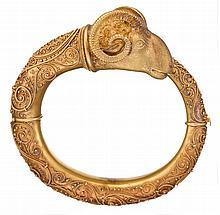 An Archaeological Revival eighteen karat gold bangle, circa 1870, designed as a by-pass bangle terminated by a ram's head with granula