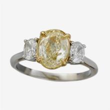 A fancy light yellow diamond, diamond, fourteen karat gold and platinum ring
