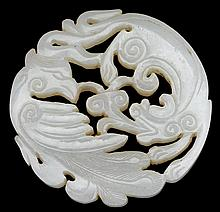Chinese white jade 'dragon and phoenix' pendant, 18th century, Circular carving of good white hue.