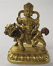Sino-Tibetan gilt bronze Vaishravana, , The diety seated on a lion and holding a mongoose dressed in armor, his face with bulging eyes
