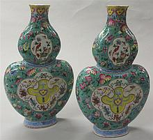 Pair of Chinese famille rose double gourd vases, 19th century, Impress moulded with shaped cartouches to depict ruyi, fu bats, birds an