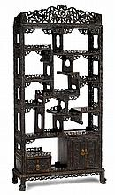 Large Chinese carved hongmu display shelf, 19th century, Shaped apron over alternating shelves, mounted with fret carved edges over two