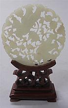 Chinese white jade circular pendant, 19th century, Pierce carved with tow boys among lotus tendrils and scrolling clouds, on wood stand