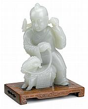 Chinese celadon jade boy carving, 19th century, Carved as a boy holding a lotus spray and the reigns to a ram by his feet; attached to