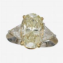 A colored diamond, diamond, eighteen karat gold and platinum ring,