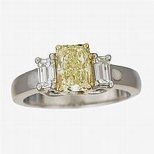 A fancy yellow diamond, diamond, eighteen karat gold and platinum ring,