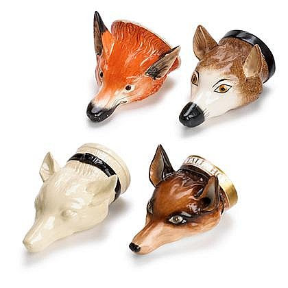 Four English creamware fox-head stirrup cups, 18th/19th century, One plain with black painted collar; one brown painted with black muzz