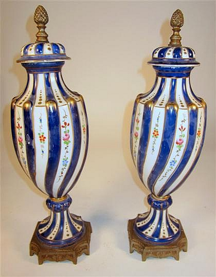 Pair of Sevres style porcelain brass mounted urns, late 19th century, Spiral baluster form, painted in cobalt and white with floral swa