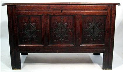English oak coffer, circa 1700, The planked rectangular top over conforming case with three carved panels, raised on stile legs.